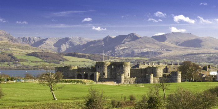 Beaumaris Castle with Snowdonia Mountains as backdrop